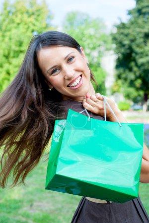 Photo pour Belle femme heureuse avec sac vert - image libre de droit