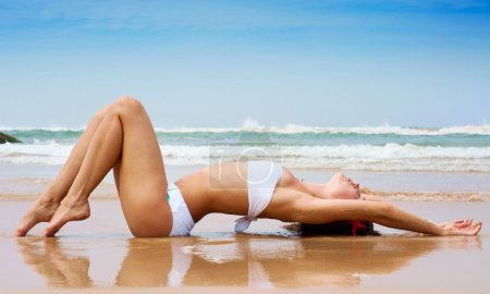 Beautiful woman lying on the wet sand