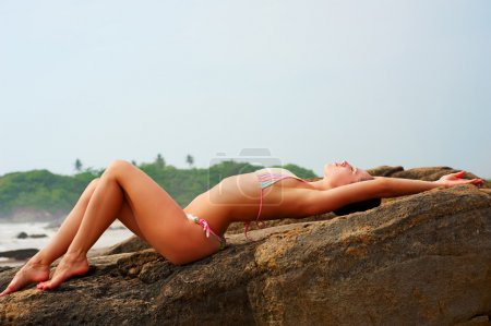 Sexy woman in bikini lying on the stone...