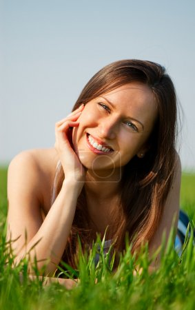 Photo for Young happy woman relaxing at the green grass - Royalty Free Image