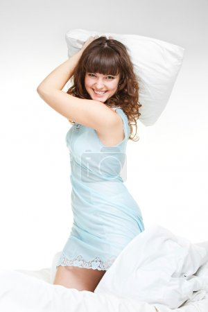 Lively young woman with pillow