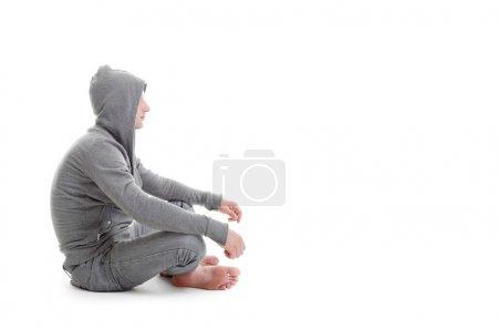 Photo pour Bel homme assis dans l'asana sur le sol blanc - image libre de droit