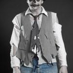 Pallid deadman in rags against dark background...