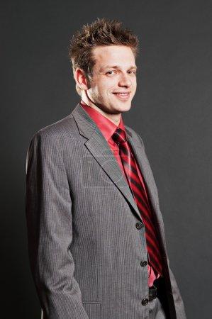 Smiley businessman in grey suit