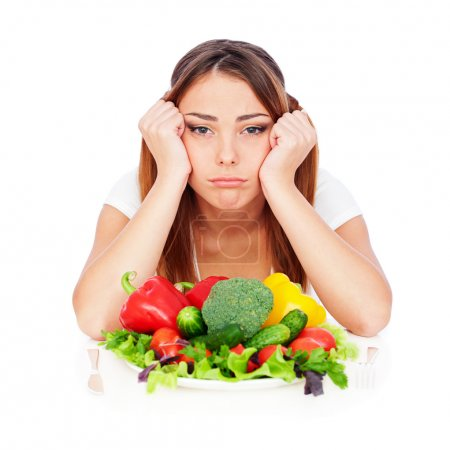 Photo for Sad woman sitting near plate with vegetables and tired from diet - Royalty Free Image