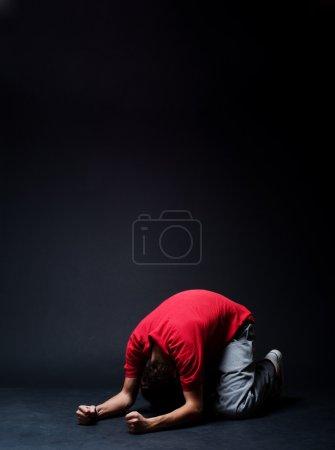 Photo pour Homme désespéré priant dans les ténèbres - image libre de droit