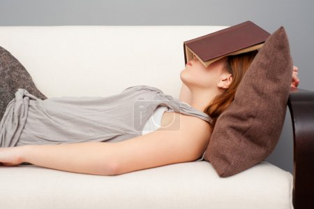 Photo for Woman sleeping with book on her face - Royalty Free Image