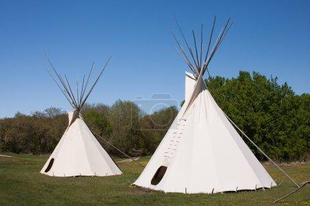 Photo pour Un petit groupe de tipis dans un pré, entouré par la forêt. tipis étaient logement traditionnel des Amérindiens dans les grandes plaines et les autres États de l'ouest. - image libre de droit