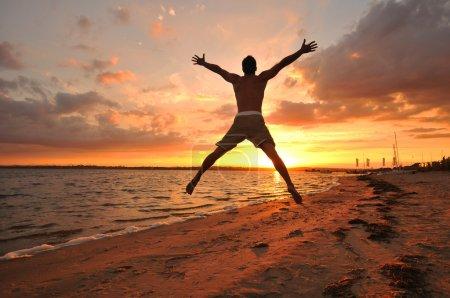 Photo pour Jeune homme sautant les bras écartés célébrant et profitant du moment au bord de la mer au coucher du soleil - image libre de droit