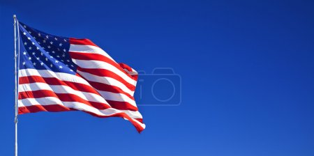 Photo for American flag fluttering in the blue sky - Royalty Free Image