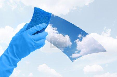 Photo pour Main dans les gants nettoyer la fenêtre avec une éponge bleue - image libre de droit