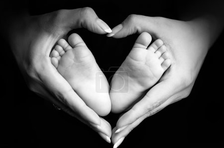 Photo for Baby's feet in mom's palms on black - Royalty Free Image