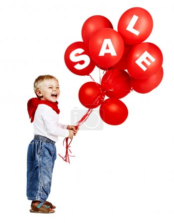 Photo for Cute little boy in white shirt, jeans and red scarf laughing as he holds a bunch of red balloons with sale sign. - Royalty Free Image