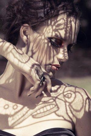 Photo pour Belle jeune femme avec des fards à paupières rouges dramatiques et de faux cils avec de l'ombre à dentelle sur son visage - image libre de droit