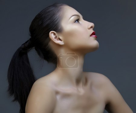 Photo for Beautiful woman with long black hair in ponytail and shiny skin looking up in profile, natural make-up and beautiful skin texture - Royalty Free Image