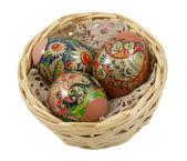 Három húsvéti tojás egy fonott kosárban felett egy fehér