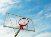 Outdoor basketball hoop over blue sky