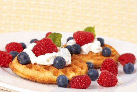 Photo for Belgian waffles with fresh raspberries, blueberries, mint leaves and cream on white plate - Royalty Free Image