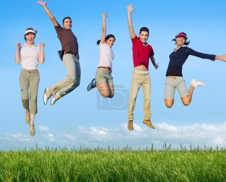 Photo for Jumping young happy group in meadow blue sky outdoor - Royalty Free Image