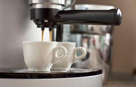 Photo pour Deux tasses d'expresso s'écoule d'une machine à expresso - image libre de droit