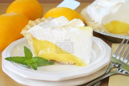 Photo pour Tranche de tarte au citron meringuée avec un morceau frais de menthe comme garniture. - image libre de droit