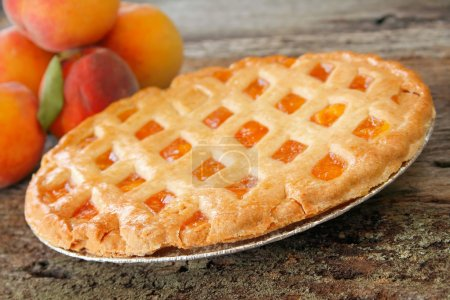 Photo for Fresh baked peach pie with fresh peaches in the background. Used a shallow depth of field with selective focus on the front edge of pie and crust. - Royalty Free Image