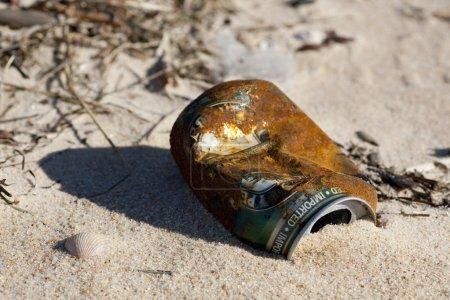Photo pour Vue rapprochée d'une canette de bière abandonnée et rouillée sur la plage . - image libre de droit
