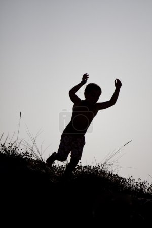 Boy jumping from a dune