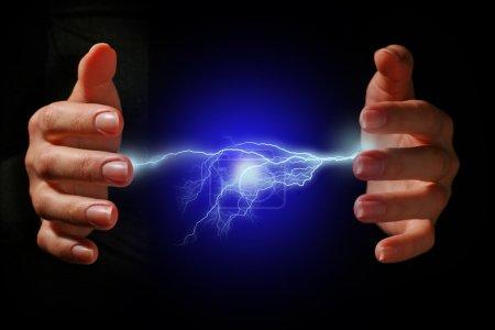 Photo pour Mains et une décharge électrique sur fond noir. - image libre de droit