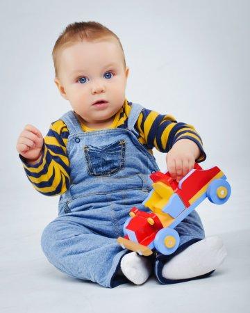 Photo pour Bébé garçon plaing sa voiture jouet en studio - image libre de droit