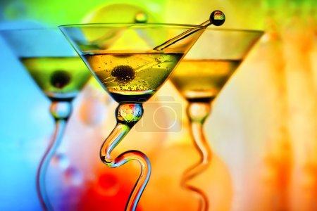 Photo pour Verres à martini belle aux olives devant fond coloré montrant les couleurs rouge, orange, bleu et vert - image libre de droit
