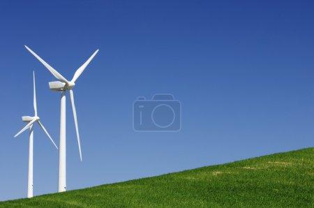 Photo pour Deux moulins à vent dans une prairie verte au ciel bleu - image libre de droit
