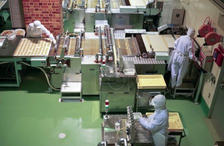 Photo pour Travailleur derrière le convoyeur dans l'atelier de l'usine de confiserie cookie de production - image libre de droit