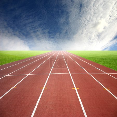 Photo for A deserted athletic running track in a green field. - Royalty Free Image