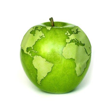 Foto de Un mapa del mundo superpuesto sobre una manzana verde. - Imagen libre de derechos