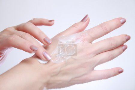 Photo for Woman applying moisturizing cosmetic creams on her hands with dry skin - Royalty Free Image